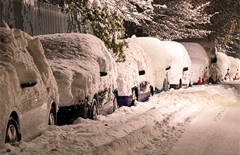 a snow covered street with parked cars